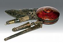 Rare nécessaire à poudre pour fusil, complet, à plusieurs éléments, en bois précieux, cuir et fer, rehaussé d'attaches en argent représentant des Gyakhils (roue de la joie).  Tibet, XVIIIe siècle.    300/500 €