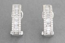 Paire de boucles d'oreilles en or gris ornées d'une ligne de diamants baguettes entre deux lignes de brillants. P. 5,6G
