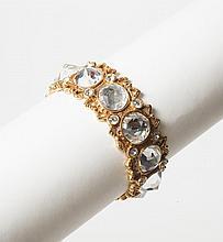 Christian DIOR Boutique    Bracelet jonc en métal doré ajouré sertis de strass à l'imitation brillant. Signé.