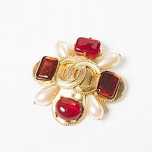 CHANEL circa 1997    Broche quadrilobée en métal doré rehaussées de cabochons en pâte de verre à l'imitation rubis et ambre, centre siglé, rehaussé de quatre gouttes de perles blanches. Bon état (légers éclats).