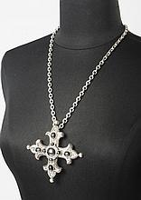 Christian DIOR Boutique    Sautoir chaine retenant un pendentif figurant une croix en métal argenté guilloché sertis de cabochons à l'imitation hématite  Signé.