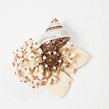 Laurence VRBA    Magnifique broche représentant un coquillage surmonté d'un bouquet de fleur en composite et perles à l'imitation ivoire, nacre, corail. Signé.