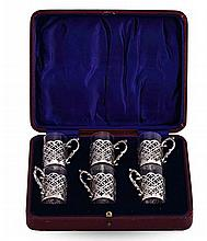 A SET OF SIX PEG GLASSES WITH SILVER HOLDERS