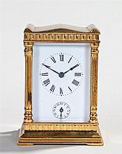 Miniature gilt metal carriage clock, the shaped top above a white enamel di