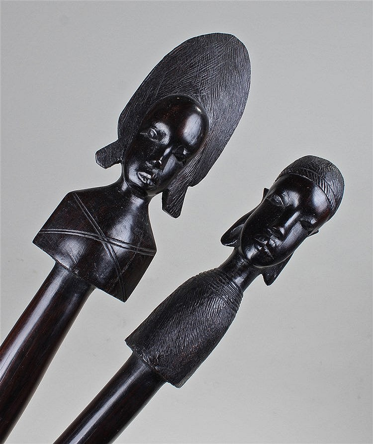 Pair of African spears, carved with a figure to each end, shaped handle and