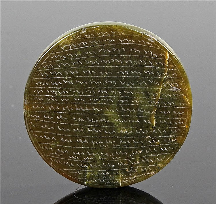 Early engraved green jade disc, with lines of designs to one side, the oppo