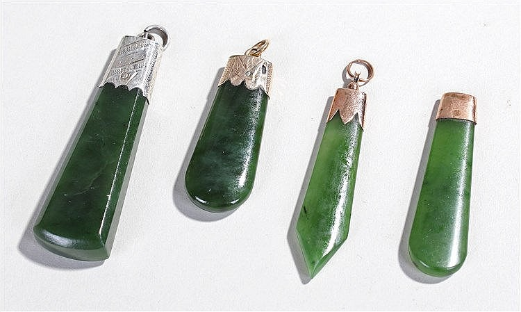 Four New Zealand Maori nephrite jade pendants, mounted on silver and gold,