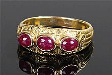 Yellow metal ruby set ring, with three cabochon ru