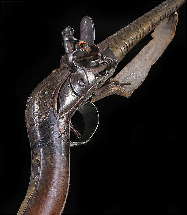 North Africa muzzel loading long gun with tapering barrel held in stock wit