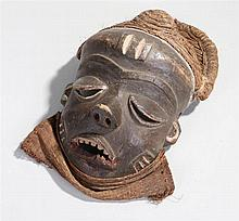 African Igbo mask, Nigeria, with a straw top above the deep eye lids, long