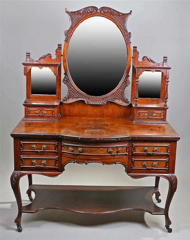 Maple & Co Edwardian walnut dressing table, the mirror back in a carved and