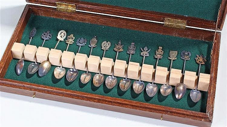 Fourteen white metal crested spoons, each with a different crest, housed wi