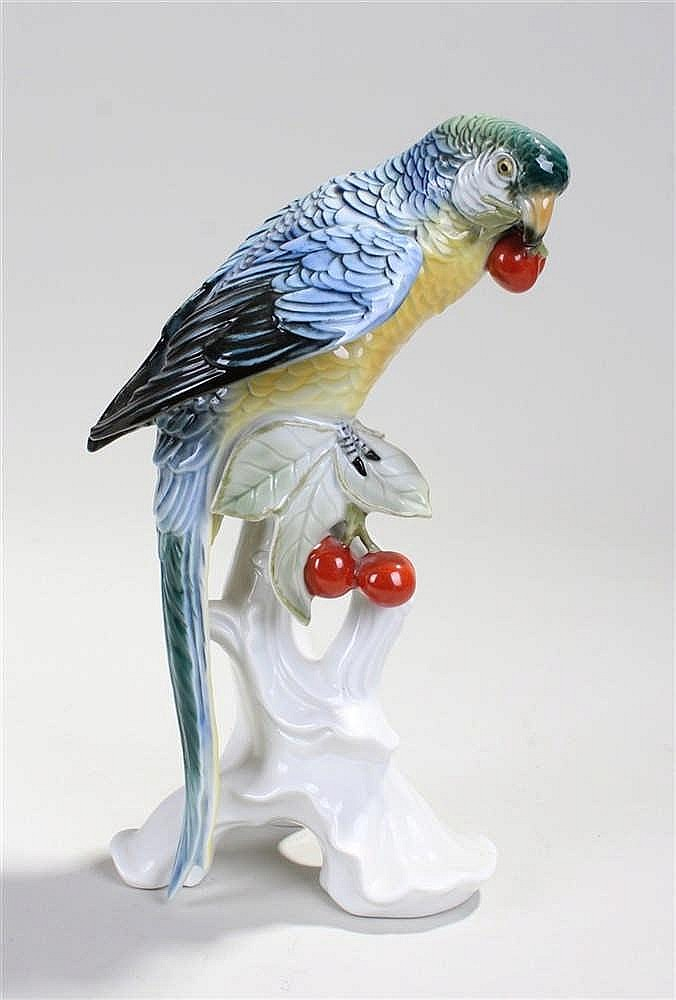 Karl Ens porcelain model of a parrot, perched on a branch eating cherries,
