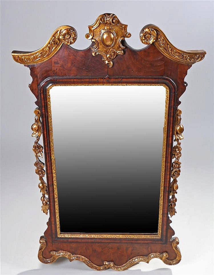 George II walnut and parcel gilt mirror, the swan neck pediment top decorat