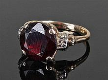 Yellow metal and garnet set ring, the central garnet with white metal shoul