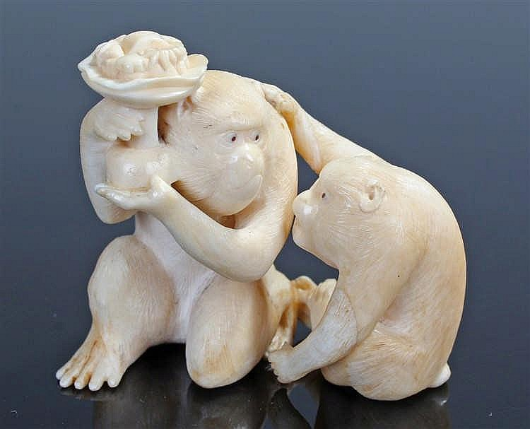 Japanese Meiji period ivory monkey group, carved as a monkey holding up a f