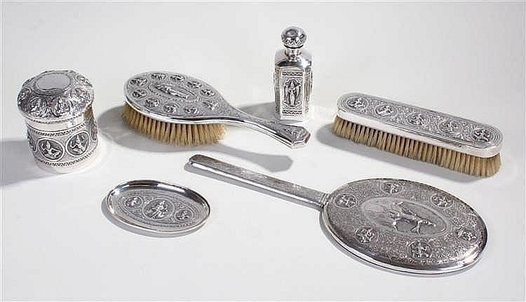 Indian white metal vanity set, to include a mirror, two brushes, a dish and