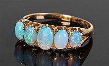 18 carat gold and opal set ring, with a row of five opals, ring size Q