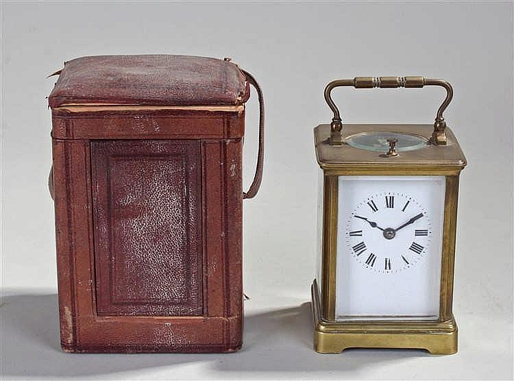 French gilt brass carriage clock, the serpentine case with a white enamel d