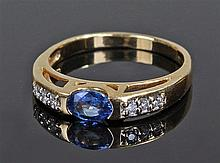 18 carat gold sapphire and diamond ring, the oval sapphire flanked by three
