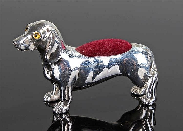A silver pin cushion in the form of a dog