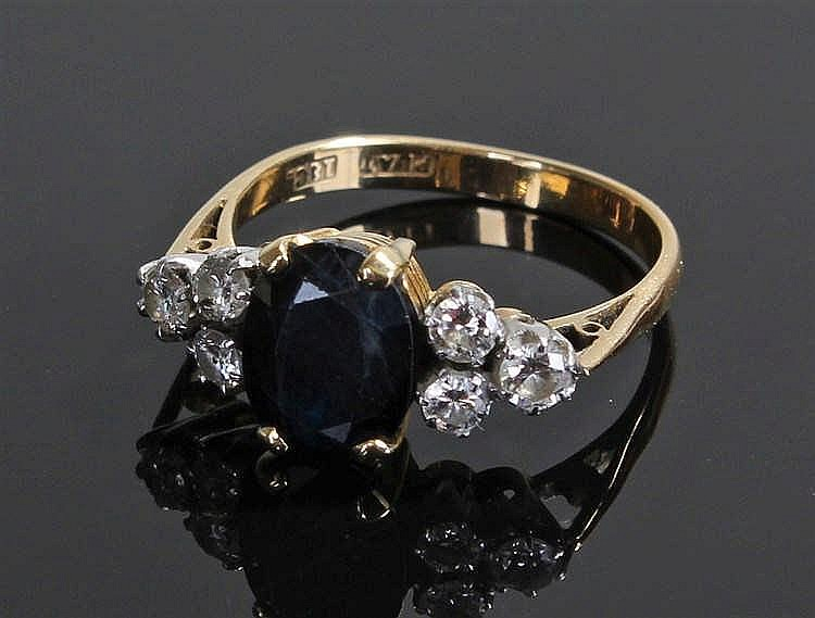 18 carat gold sapphire and diamond ring, the central sapphire flanked with