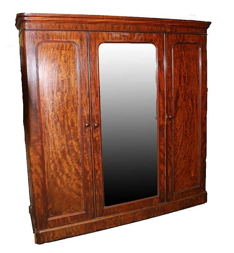Victorian mahogany triple wardrobe, the large central mirrored door enclosi