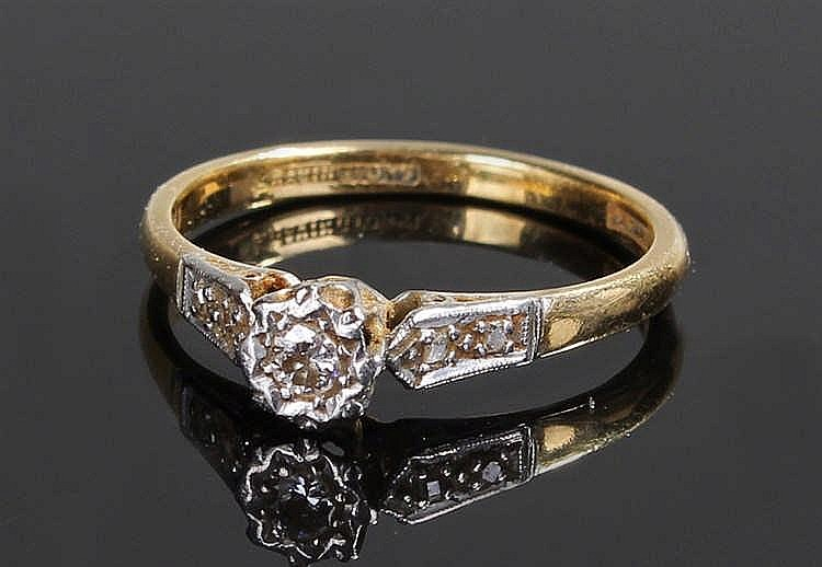 18 carat gold, diamond set ring, the central diamond flanked with a platinu