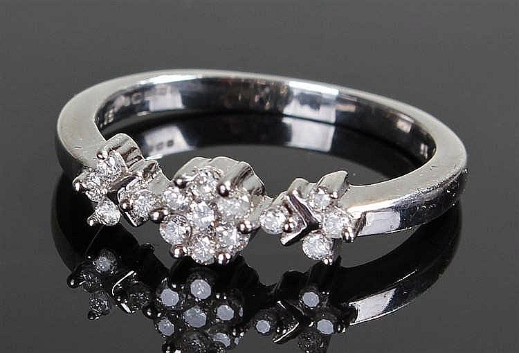 9 carat white gold and diamond ring, with a flower head center flanked by t