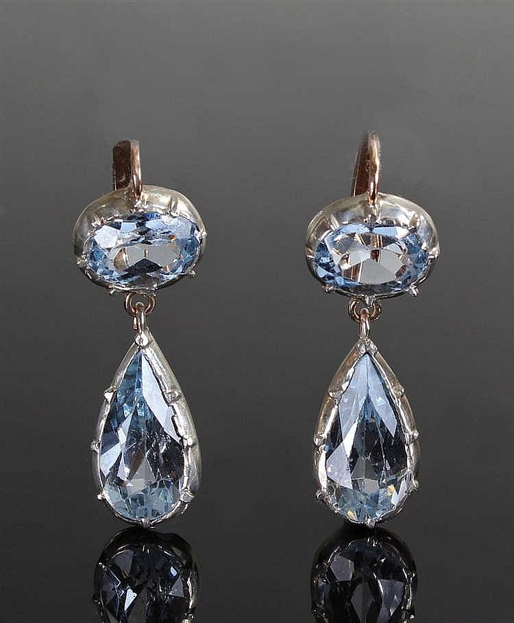 Pair of blue topaz earrings, set with an oval and pear cut topaz to each ea