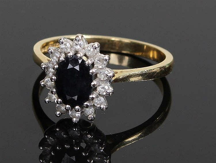 18 carat gold sapphire and diamond ring, the central sapphire surrounded by