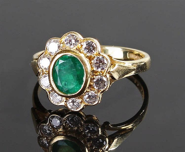 18 carat gold emerald and diamond ring, the central oval cut emerald at 0.6