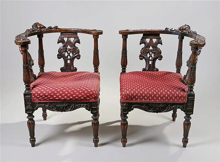 Pair of Edwardian carved corner chairs, each carved with the face of putti