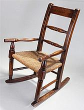 Child's oak rocking chair, the bar back with turned spindles above a rush s