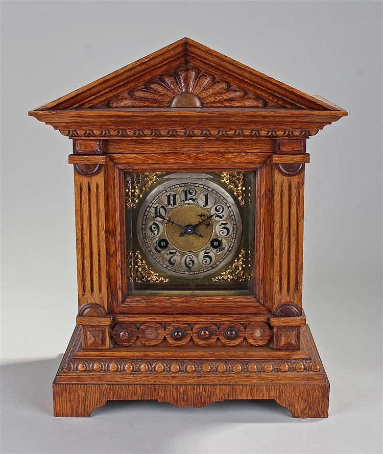 Early 20th Century oak cased mantel clock, the arched top with sunburst pan