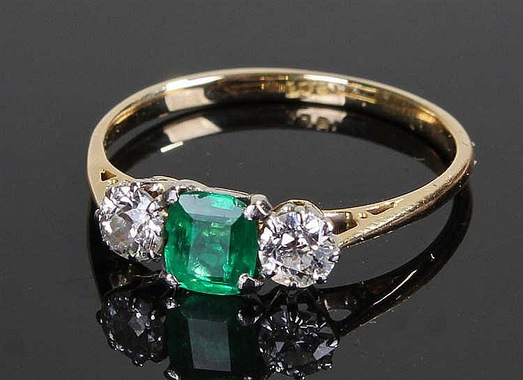 18 carat gold diamond and emerald set ring, the central emerald flanked by