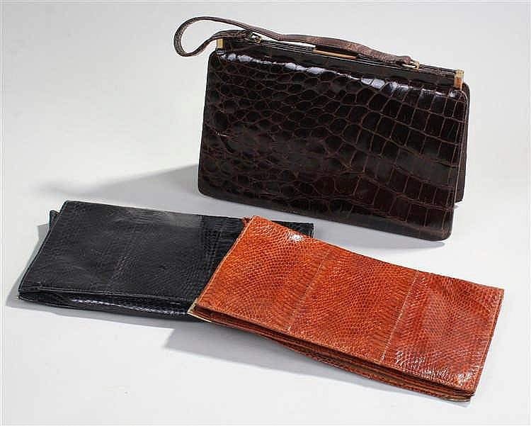 Two snakeskin clutch bags, in black and brown, together with a leather hand