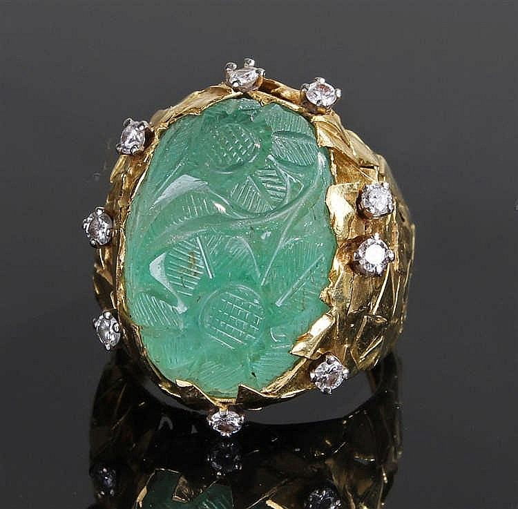 Unusual carved emerald and diamond set ring, the emerald at 20mm in length