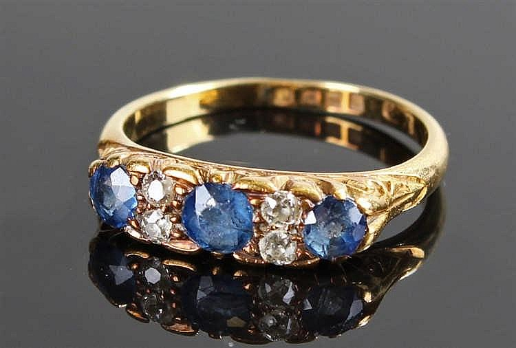 Sapphire and diamond ring, the central round faceted sapphire flanked by tw