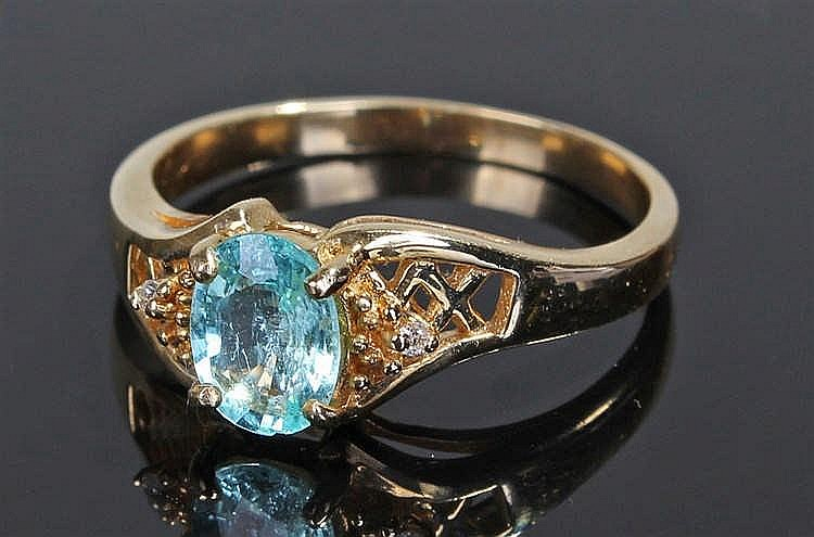 18 carat gold, pale blue zircon ring, the oval cut zircon flanked by a diam