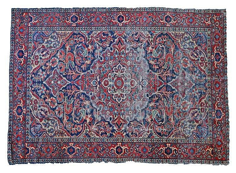 Persian rug, decorated with stylised foliage in muted shades of red and blu