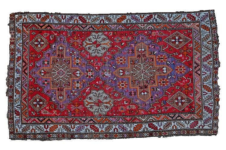 Persian rug, the geometric design interior in shades of red and purple bord