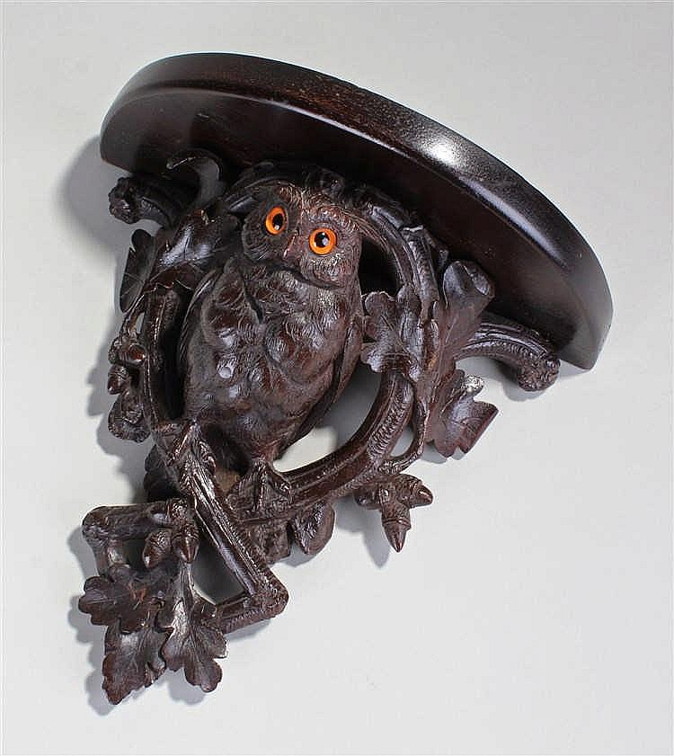 Black Forest carved bracket, in the form of an owl with orange eyes resting