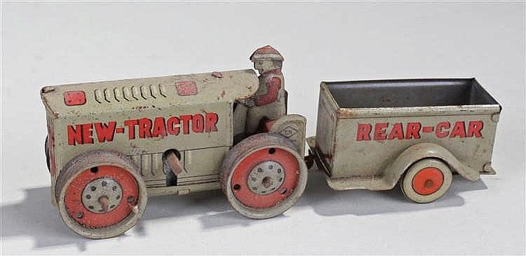Tinplate clockwork toy of a New-Tractor and Rear-Car, in grey with red lett