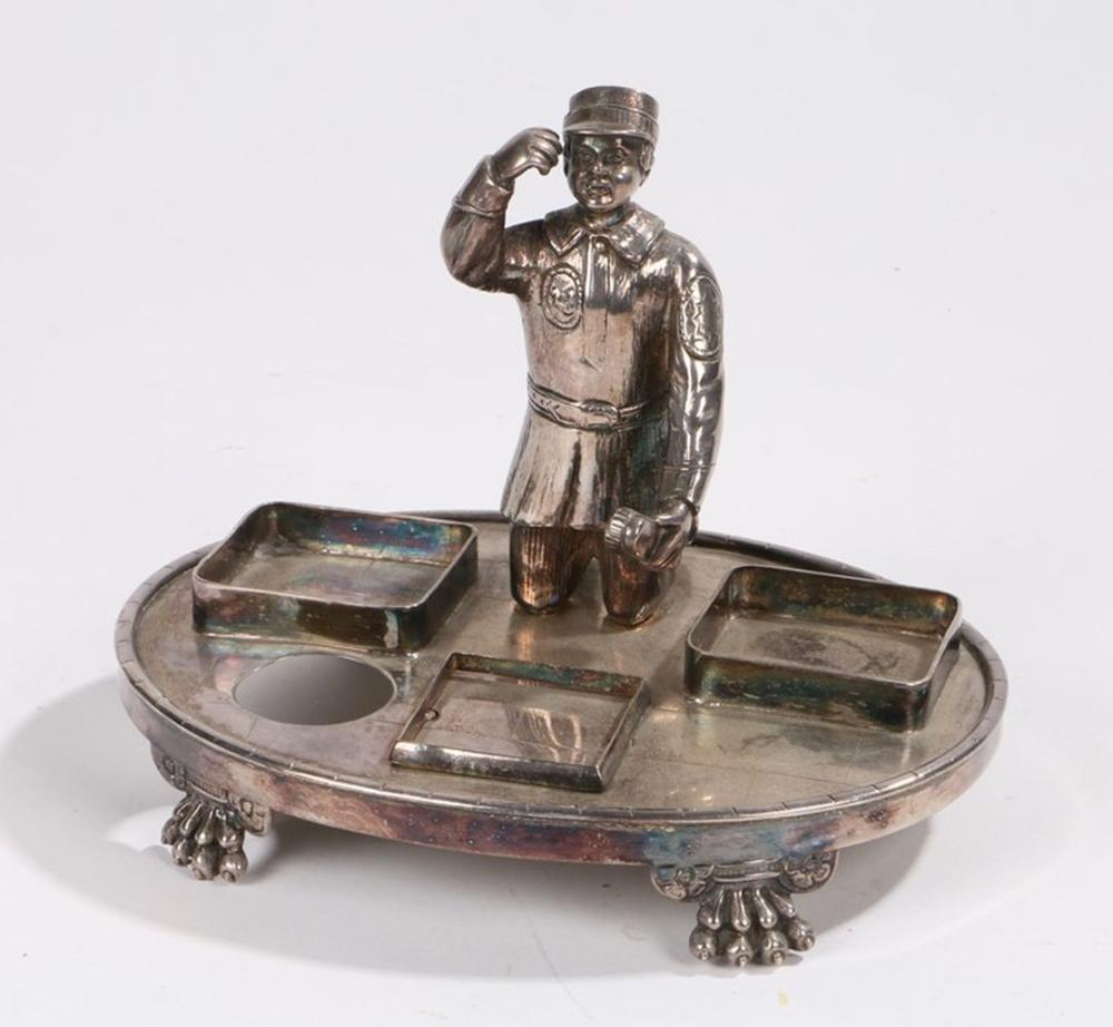 Silver plated desk stand, of oval form with central depiction of a shoe shine boy doffing his cap, s