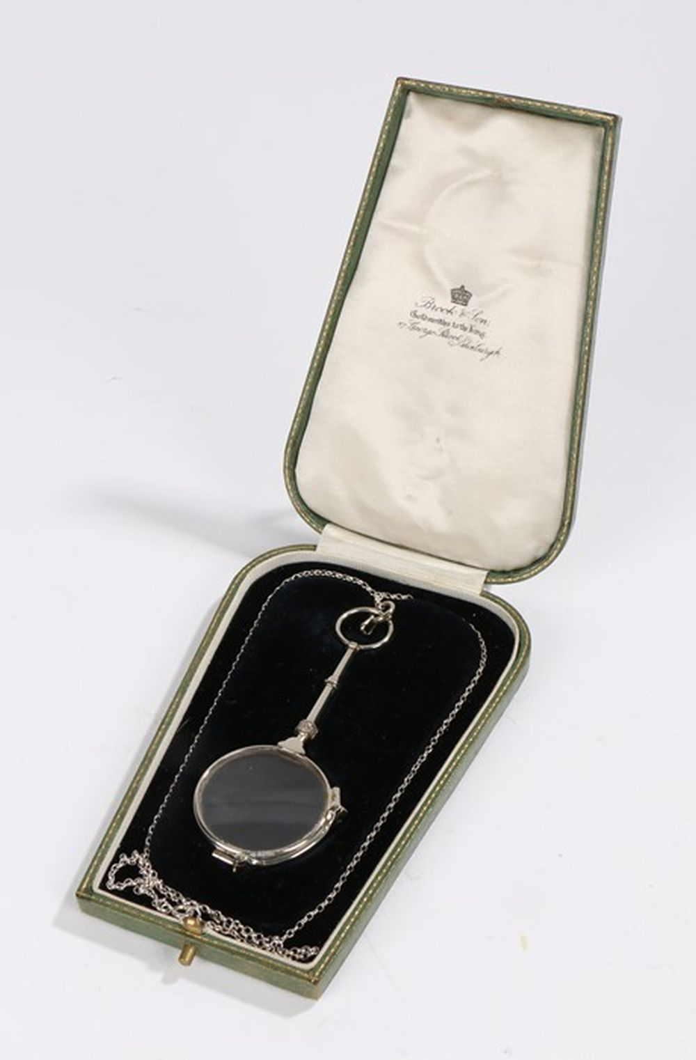 Pair of Continental white metal folding glasses, on a white metal chain, housed in a black velvet li