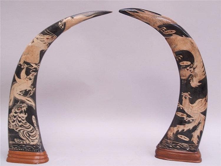 Paar Hornschnitzereien(Hochlandochsen) - 20 Jhdt. Südostasien, aufwendige Schnitzereien mit Phoenix, Tiger und Drachen,auf Holzsockel montiert,H.ca. 46cm,ein Horn lt. best. an der Spitze