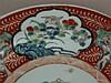 Teller - China,19./20.Jh.,Bemalung mit polychromen Emaillefarben im Imari-Stil,Fahne unterseitig mit Wolken-und Fledermaus-Motiven,unterseitig 6-Zeichnen-Kaishu-Marke,kl.Brandfehler,D .ca.26cm