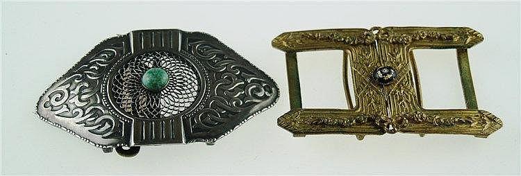 2 Gürtelschnallen- 1x versilbert mit kl. Stein in der Mitte, aufwändig gearbeitet mit ornamentalem Durchbruch und Reliefdekor,1x Messing mit Lapis und Emaille-Zier