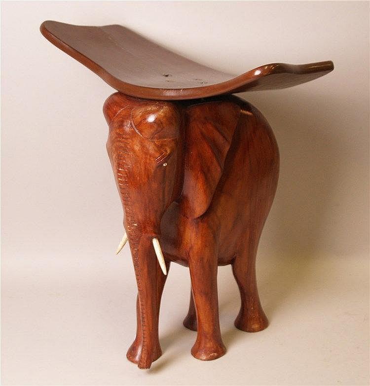 Hocker ''Elefant'' - Holz, H.ca.51cm, gebogte Sitzfläche ca.24x44cm,eingelegte Augen und Steckzähne aus Bein, Gebrauchs- u.Altersspuren, einige Schädigunen am Elephant-Korpus und Sitzbrett